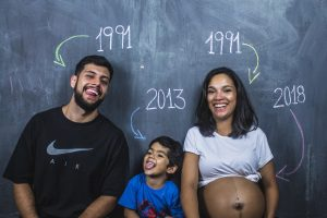 Pregnancy announcement with father, son, and mother