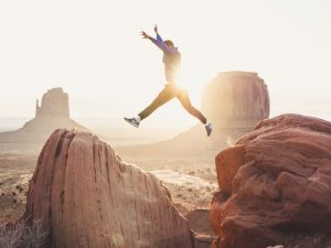 Arizona desert man leaping from one rock to another